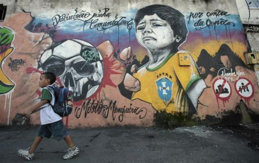 A boy walks in front of graffiti painted against infrastructure work for the 2014 World Cup at the Metro Mangueira slum in Rio de Janeiro