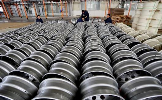 Workers arrange steel rims for export at a wheel factory in Lianyungang