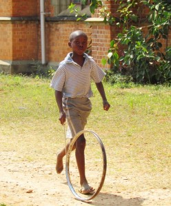 boy playing with old bicycle steel rim and stick